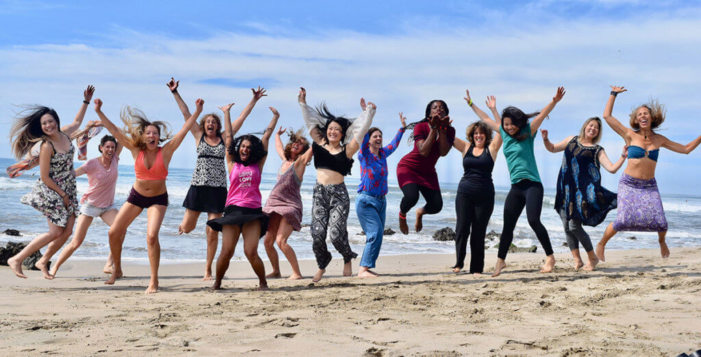 A fun group retreat of women leap in the air with the ocean behind them