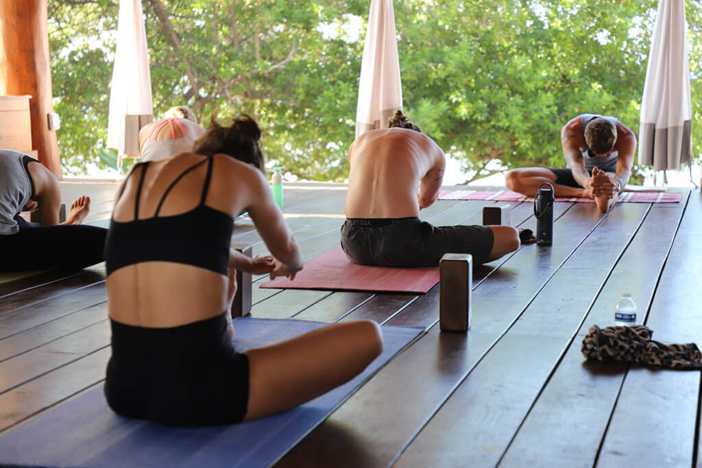 A group yoga class practices a forward bend