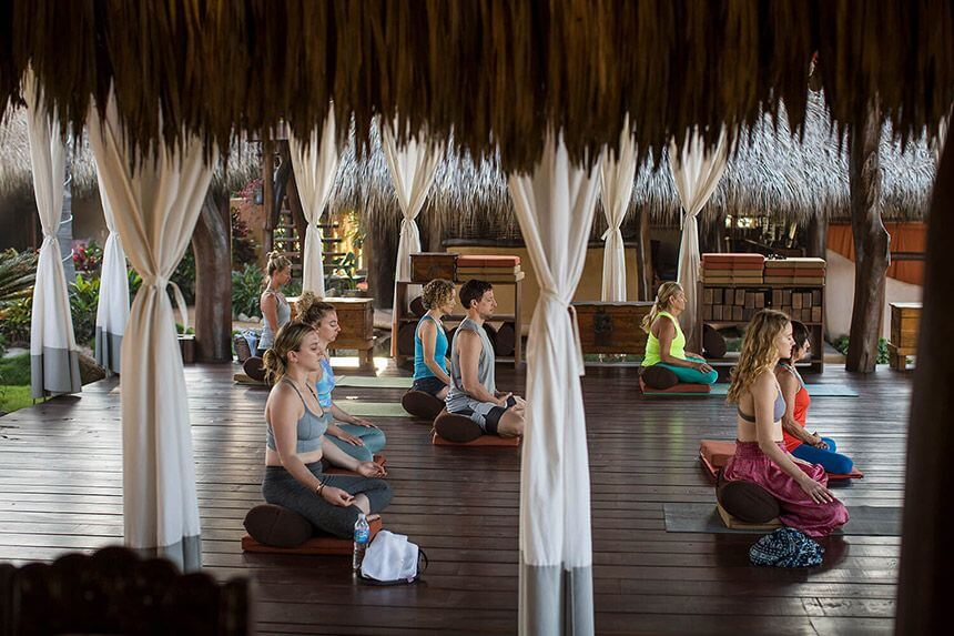 A class sits in the yoga pavillion and quietly meditates